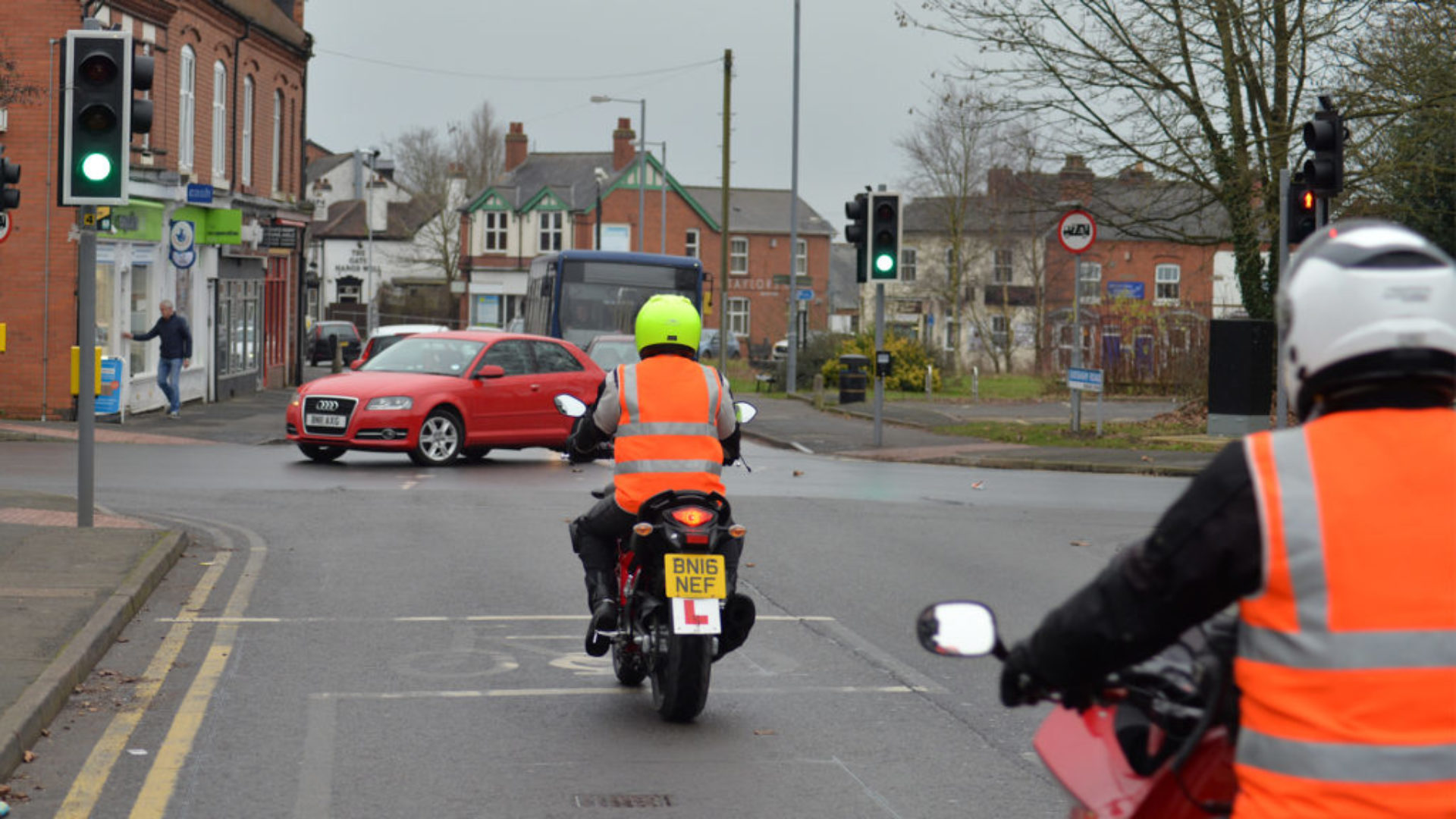 Female student training towards her Mod 2 (Module 2) test with her instructor, crossing traffic lights