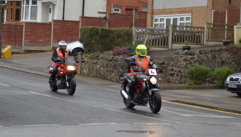 Learner rider at junction, with her instructor, turning right, minor to major